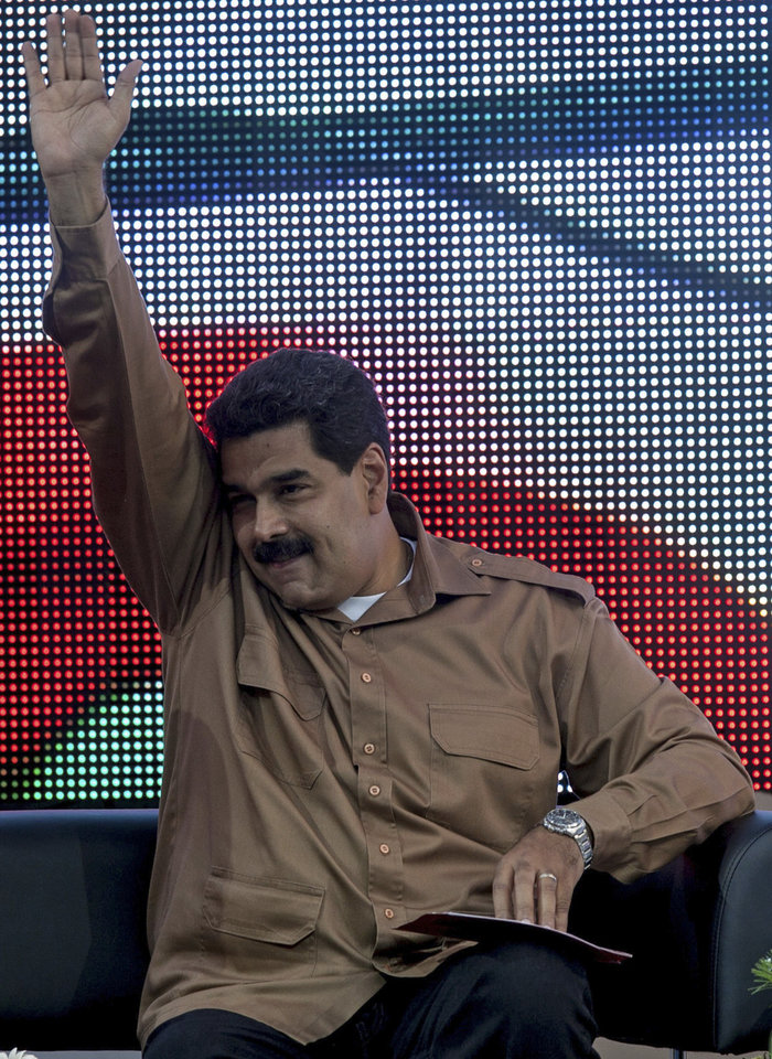 Photo - Venezuela's President Nicolas Maduro greets supporters as he arrives at rally in Bolivar Square to commemorate International Women's Day in Caracas, Venezuela, Saturday, March 8, 2014. Maduro's government celebrated an Organization of American States declaration supporting its efforts to bring a solution to the country's worst political violence in years, calling it a diplomatic victory. The United States, Canada and Panama were the only nations to oppose the declaration. Meanwhile street protests continue almost daily while the opposition sits out a peace process it calls farcical. (AP Photo/Alejandro Cegarra)
