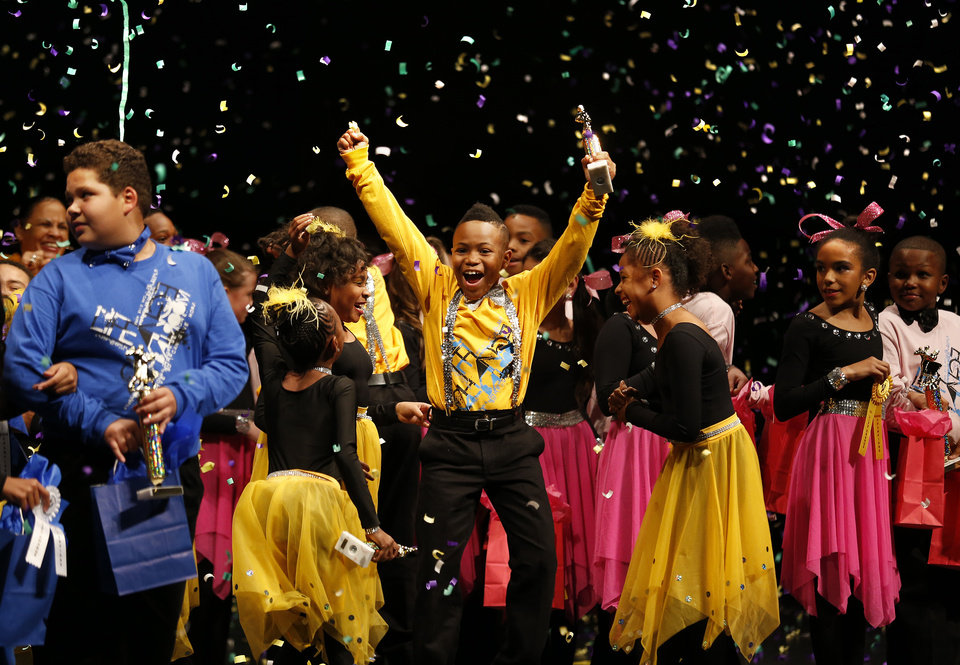 Photo -  Millwood Arts Academy's Zion Mason, center, celebrates Thursday after his team won the LifeChange Ballroom competition at the Rose State Performing Arts Theatre in Midwest City.   Sarah PHIpps -  Sarah Phipps