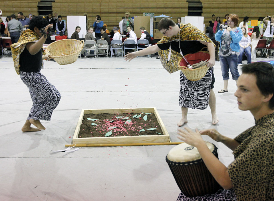 Photo - Representing West Africa, Hunter Billen plays a drum while Roshin Papaly, left, and Nathan Kelly dance during Monday's Global Festival in Midwest City. Photos By Paul Hellstern, The Oklahoman