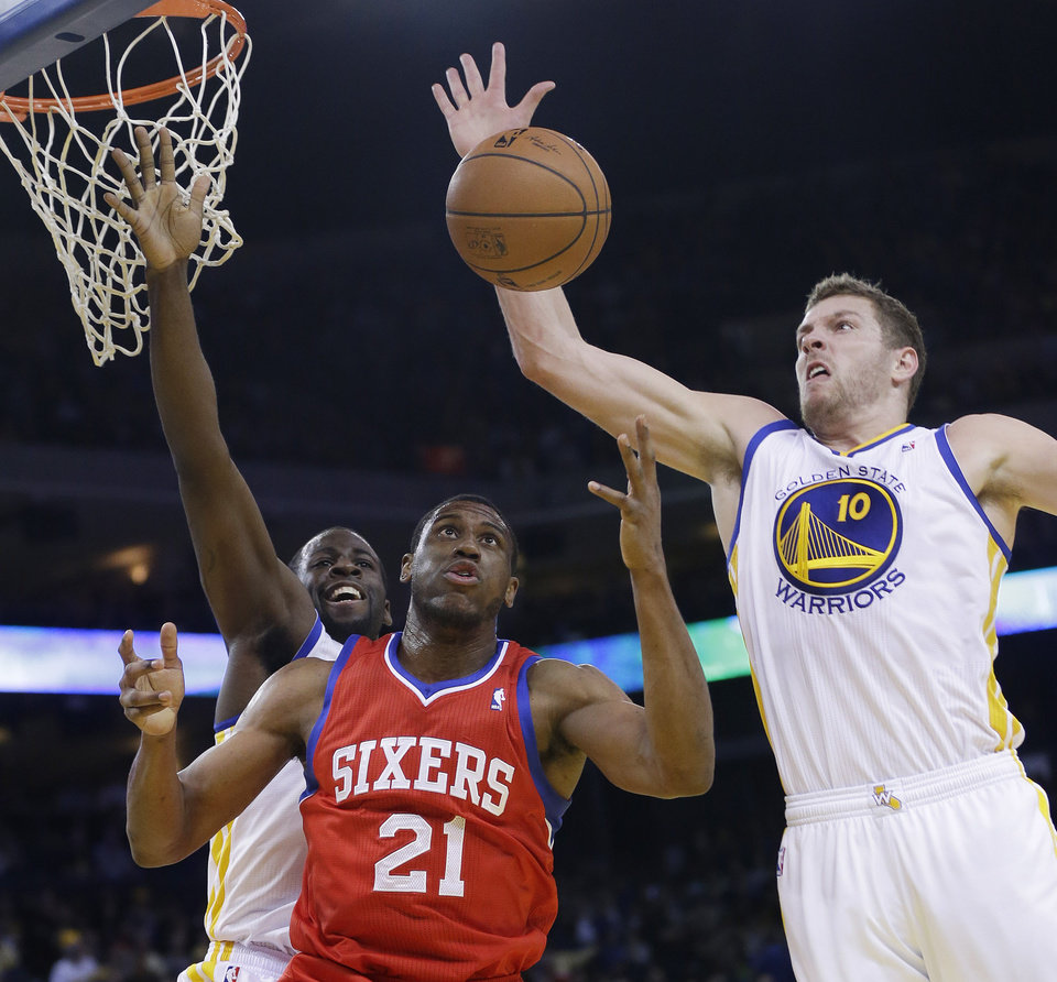 Photo - Golden State Warriors' David Lee (10) grabs a rebound next to Philadelphia 76ers' Thaddeus Young (21) and teammate Draymond Green, left, during the first half of an NBA basketball game, Monday, Feb. 10, 2014, in Oakland, Calif. (AP Photo/Marcio Jose Sanchez)