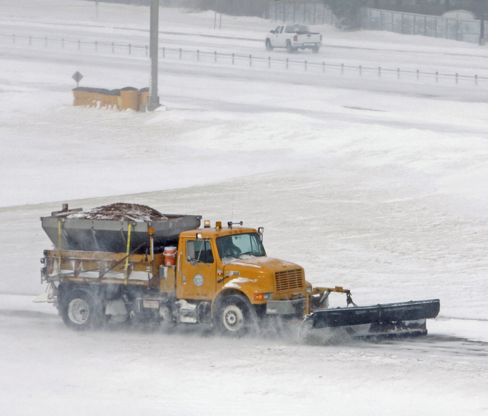 Photo - A snow plow clears the entrance ramp to I 35 at Lindsey Street after an epic winter storm on Tuesday, February 1, 2011, in Norman, Okla.  Photo by Steve Sisney, The Oklahoman