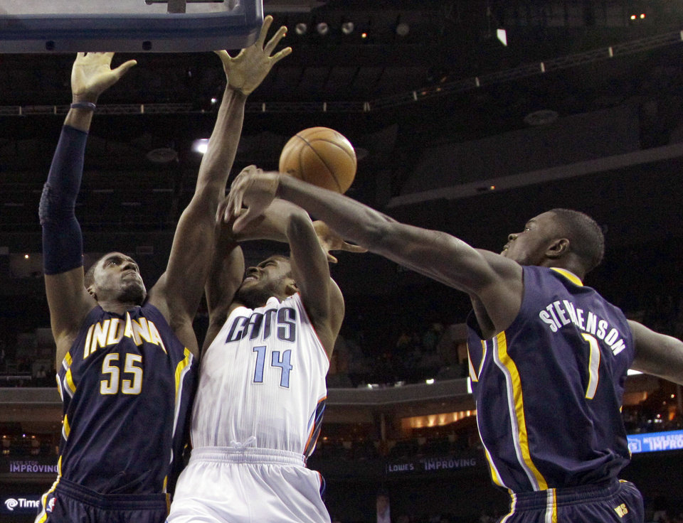 Charlotte Bobcats' Michael Kidd-Gilchrist (14) is fouled as he drives between Indiana Pacers' Lance Stephenson (1) and Roy Hibbert (55) during the first half of an NBA basketball game in Charlotte, N.C., Tuesday, Jan. 15, 2013. (AP Photo/Chuck Burton)