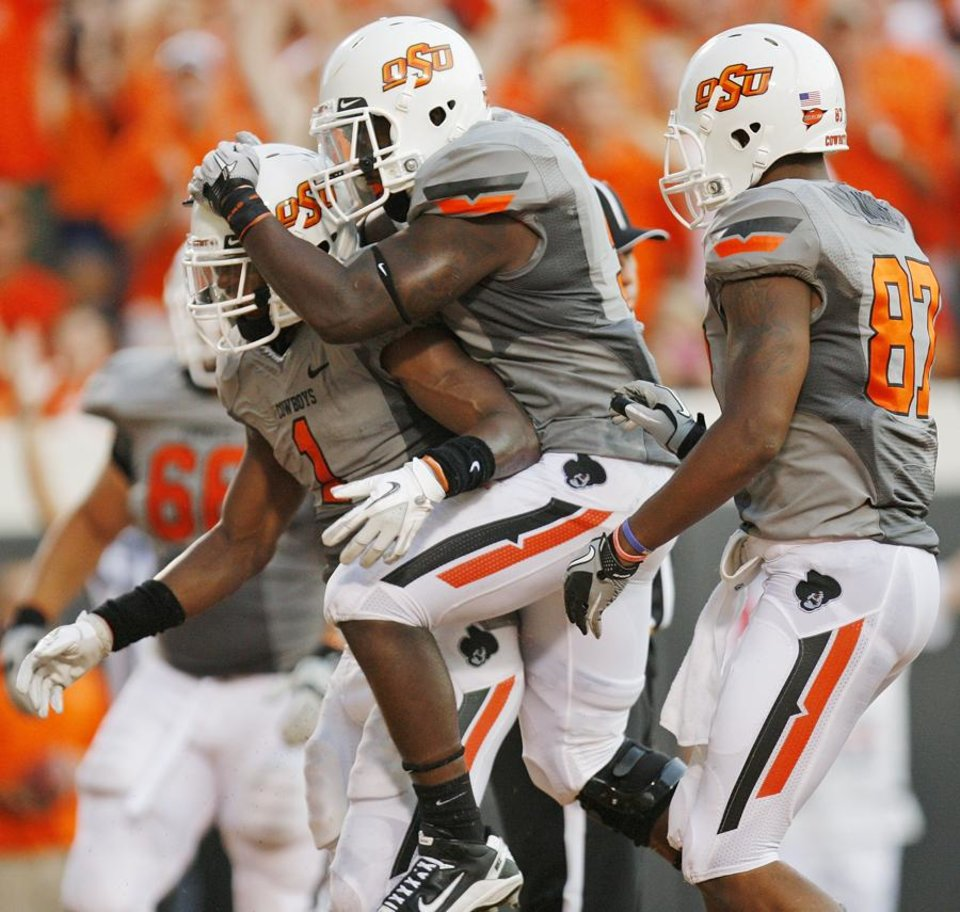 Photo -  OSU's Kye Staley (9), middle, leaps on the back of Joseph Randle (1) in front of Tracy Moore (87) as they celebrate a touchdown run by Randle in the second quarter during a college football game between the Oklahoma State Cowboys (OSU) and the University of Louisiana at Lafayette (ULL) Ragin' Cajuns at Boone Pickens Stadium in Stillwater, Okla., Saturday, Sept. 3, 2011. Photo by Nate Billings, The Oklahoman ORG XMIT: KOD