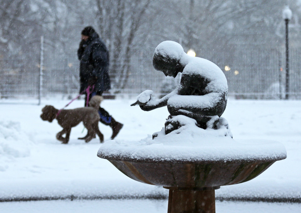 "A man walks his dog past the snow covered ""Boy and Bird"" fountain in the Boston Public Garden in Boston, Friday, Feb. 8, 2013. Mass. Gov. Deval Patrick declared a state of emergency Friday and banned travel on roads as of 4 p.m. as a blizzard that could bring nearly 3 feet of snow to the region began to intensify. As the storm gains strength, it will bring ""extremely dangerous conditions"" with bands of snow dropping up to 2 to 3 inches per hour at the height of the blizzard, Patrick said. (AP Photo/Charles Krupa) ORG XMIT: MACK106"