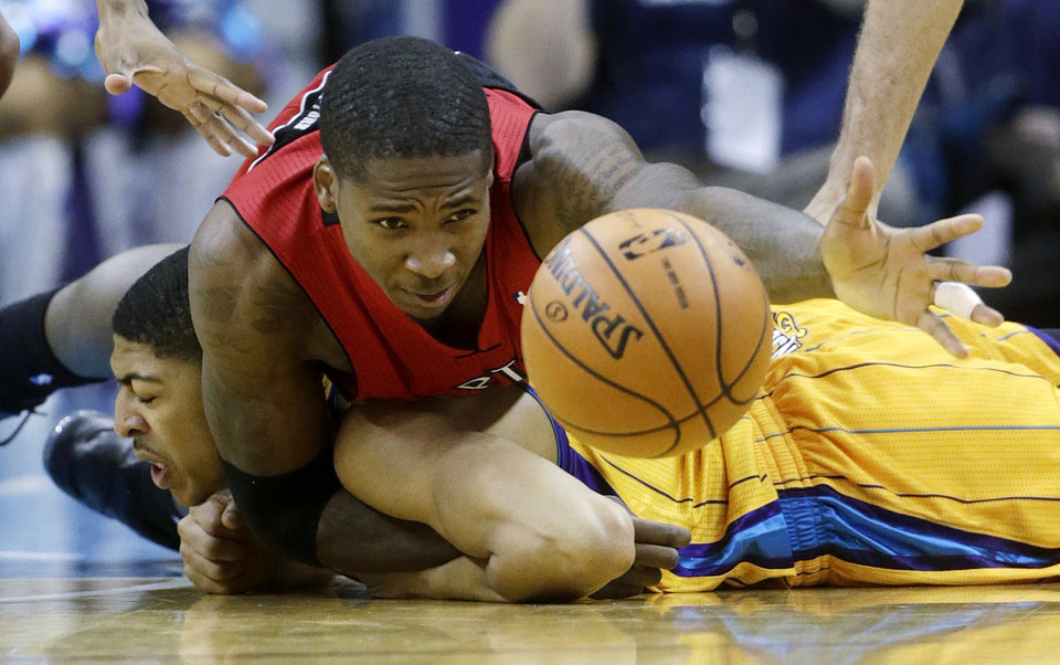 Toronto Raptors forward Ed Davis, top, fights for the loose ball with New Orleans Hornets forward Anthony Davis (23) during the third quarter of an NBA basketball game in New Orleans, Friday, Dec. 28, 2012. (AP Photo/Dave Martin)