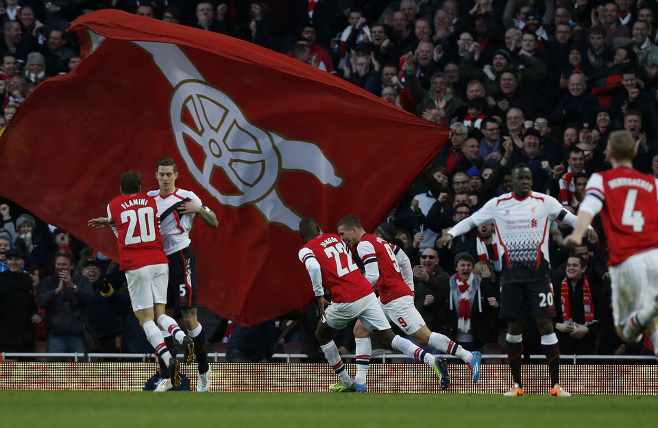 Photo - Arsenal's Lukas Podolski, center right, celebrates his goal against Liverpool with teammates during their English FA Cup fifth round soccer match at Emirates Stadium in London, Sunday, Feb. 16, 2014. (AP Photo/Sang Tan)
