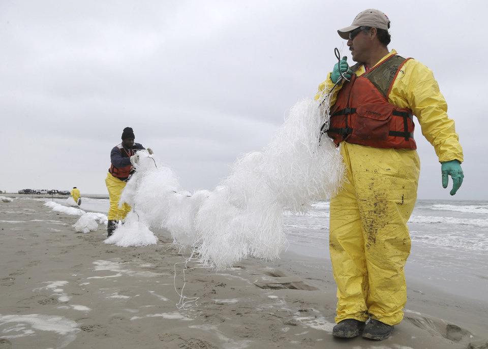 Photo - Oil spill clean up workers spread viscous snare line along East Beach in Galveston, Texas, to snag oil Monday, March 24, 2014. Thousands of gallons of tar-like oil spilled into the major U.S. shipping channel after a barge ran into a ship Saturday. (AP Photo/Pat Sullivan)