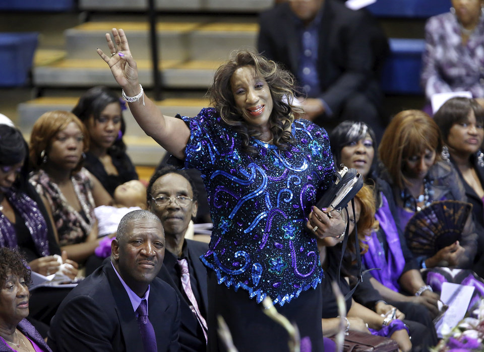 Daughter Patricia Myles stands and raises her arm as vocalist Rosie Kay Gross sings