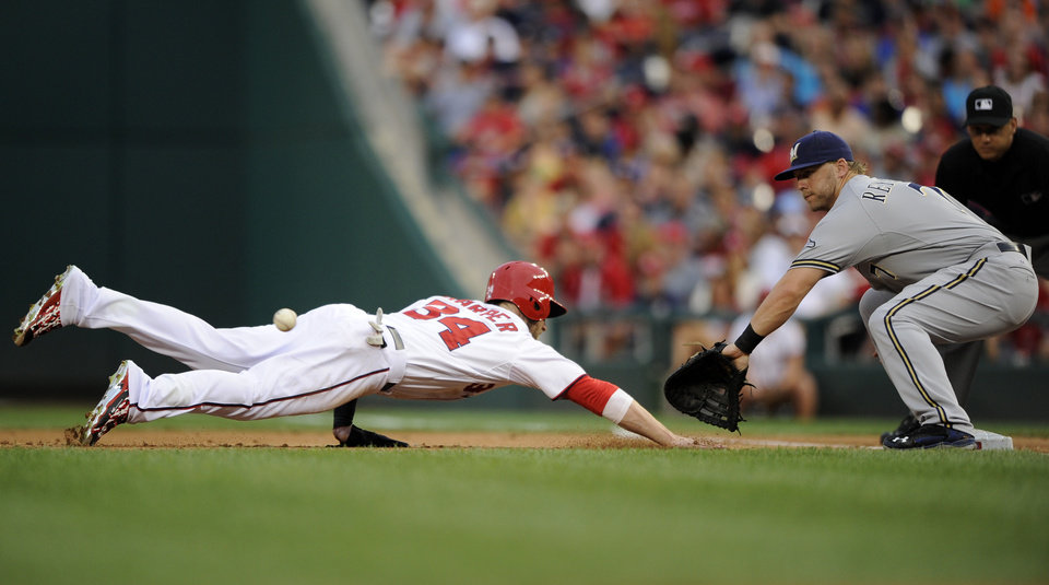 Photo - Washington Nationals' Bryce Harper (34) dives back safely to first on a pickoff attempt as Milwaukee Brewers first baseman Mark Reynolds (7) awaits the ball during the second inning of a baseball game, Friday, July 18, 2014, in Washington. (AP Photo/Nick Wass)