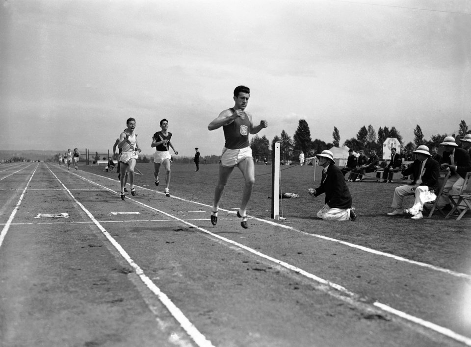 Photo - FILE - In a May 20, 1939 file photo, Louis Zamperini of he University of Southern California, breaks the tape and record with a time of 4:16.3 to win the mile run in the Pacific Coast Conference Track and Field meet the University of Washington Stadium in Seattle. Leo Girard, of Stanford, left, was second and Cole, of California, second from left, was third. Zamperini, a U.S. Olympic distance runner and World War II veteran who survived 47 days on a raft in the Pacific after his bomber crashed, then endured two years in Japanese prison camps, died Wednesday, July 2, 2014, according to Universal Pictures studio spokesman Michael Moses. He was 97.  (AP Photo/Paul Wagner, File)
