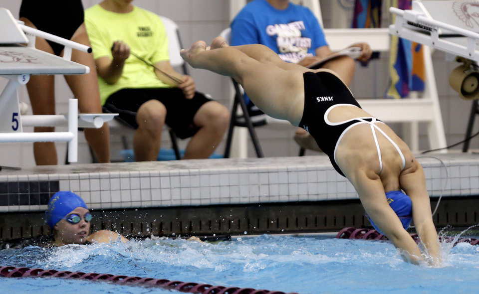 Photo - East swimmer Hailey Jensen (left) watches as teammate Kathy Bliss dives into the pool  in the girls 200 yard medley relay, during all-state swim meet, at the Jenks Trojan Aquatic Center, on Monday, July 29, 2013. CORY YOUNG/Tulsa World