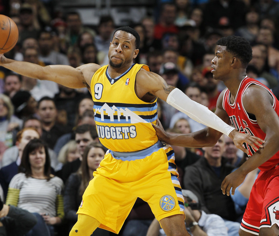 Photo - Denver Nuggets guard Andre Iguodala, left, reaches out ot pull in a loose ball as Chicago Bulls guard Jimmy Butler covers in the first quarter of an NBA basketball game in Denver on Thursday, Feb. 7, 2013. (AP Photo/David Zalubowski)