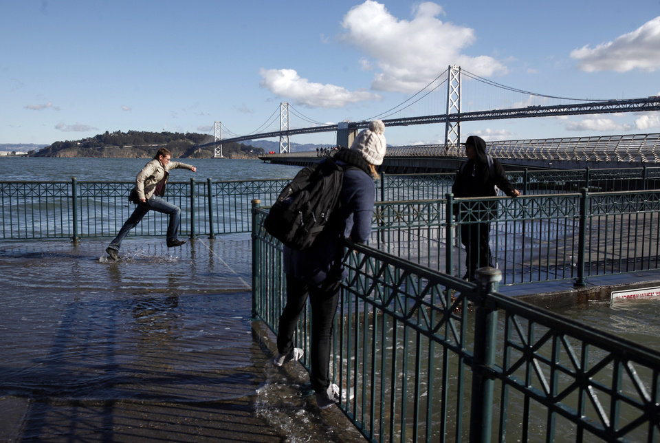 Photo - Pedestrians cannot resist getting close to Thursday's king's tide cresting along the San Francisco Embarcadero on Thursday, Dec. 13, 2012. The tide measured 7.2 at the Golden Gate and was the highest of the year. The king tides are expected to peak during the next several days, with surges over 9 feet in some areas. The phenomenon is caused by a unique alignment of the sun, moon and earth.  (AP Photo/Bay Area News Group, Karl Mondon)  MAGS OUT; NO SALES