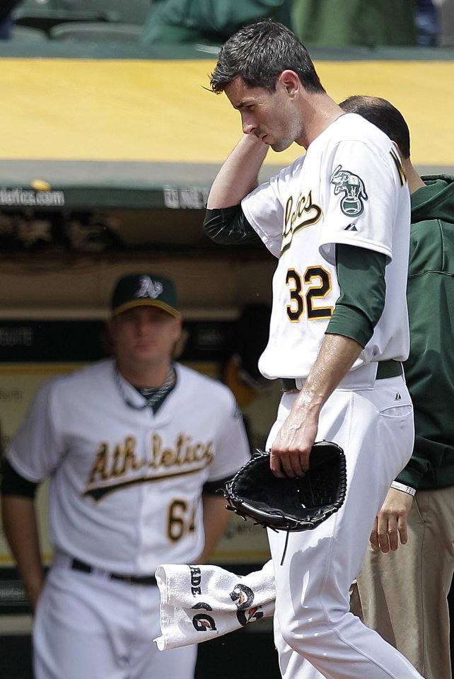 Photo -   In this photo from Wednesday, Sept. 5, 2012, Oakland Athletics pitcher Brandon McCarthy (32) places his hand to his head as he leaves the baseball game against the Los Angeles Angels in Oakland, Calif. McCarthy remains in a ''life-threatening'' situation in a Bay Area hospital two days after being hit in the head by a line drive. Struck on the right side of his head by a hard shot from the Angels' Erick Aybar, McCarthy suffered an epidural hemorrhage, brain contusion and skull fracture. He had two hours of surgery to relieve pressure on his brain late Wednesday night. A's athletic trainer Nick Paparesta was asked Friday if McCarthy was still in a life-threatening situation.