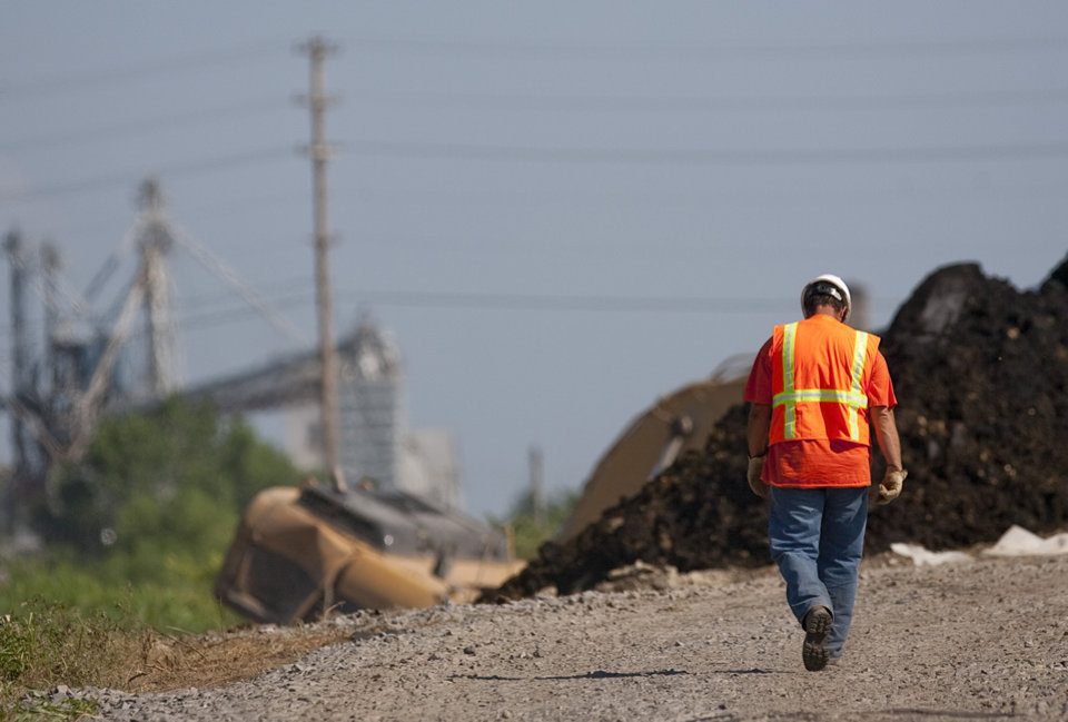 A construction worker walks towards a pile of tar and a backhoe. Clean up is taking place at the Cushing, Okla Superfund site on Tuesday June 22, 2009. Photo by Mitchell Alcala, The Oklahoman ORG XMIT: KOD