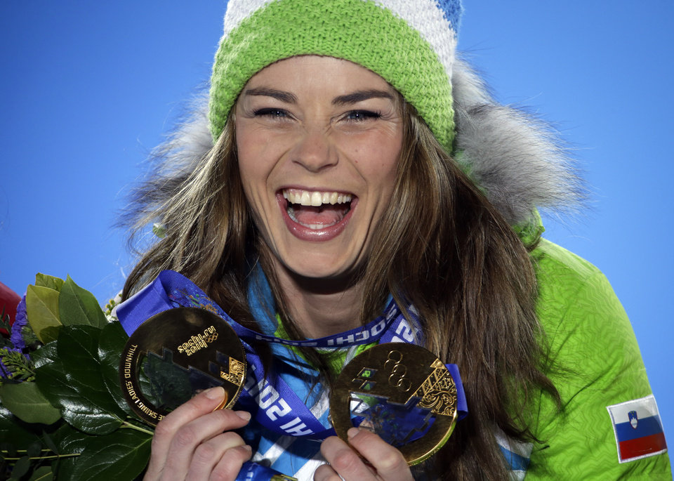 Photo - Women's giant slalom gold medalist Tina Maze of Slovenia, who also won the gold in the women's downhill, poses with her medals at the 2014 Winter Olympics, Wednesday, Feb. 19, 2014, in Sochi, Russia. (AP Photo/David Goldman)