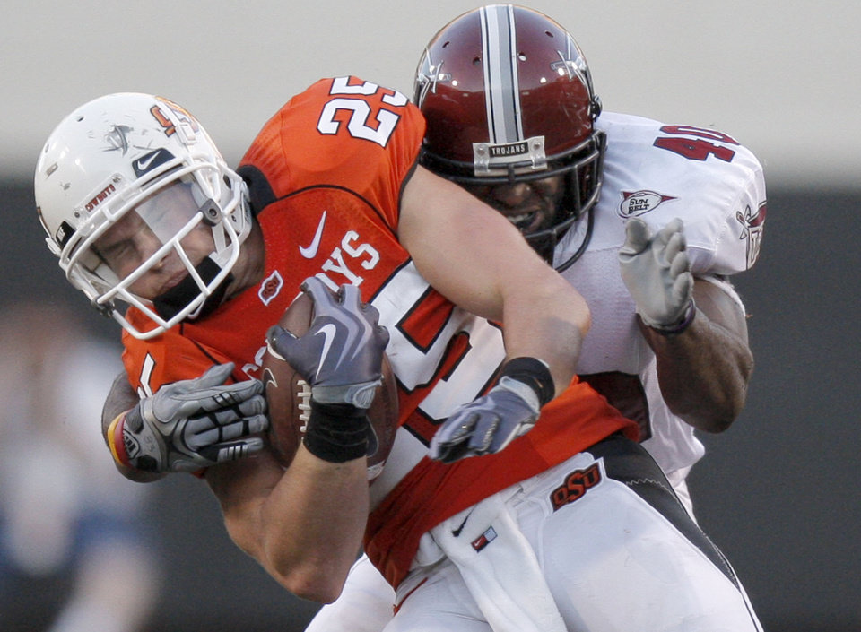 Photo - OSU's Josh Cooper (25) is tackled by Troy's Donnell Golden (40) during the college football game between the Oklahoma State University Cowboys (OSU) and the Troy University Trojans at Boone Pickens Stadium in Stillwater, Okla., Saturday, Sept. 11, 2010. Photo by Sarah Phipps, The Oklahoman