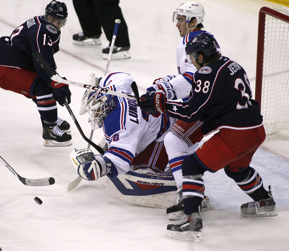 Photo - New York Rangers goalie Henrik Lundqvist (30) dives for the puck during the third period of an NHL hockey game against the Columbus Blue Jackets, Friday, March 21, 2014, in Columbus, Ohio. The Rangers won 3-1.  (AP Photo/Mike Munden)
