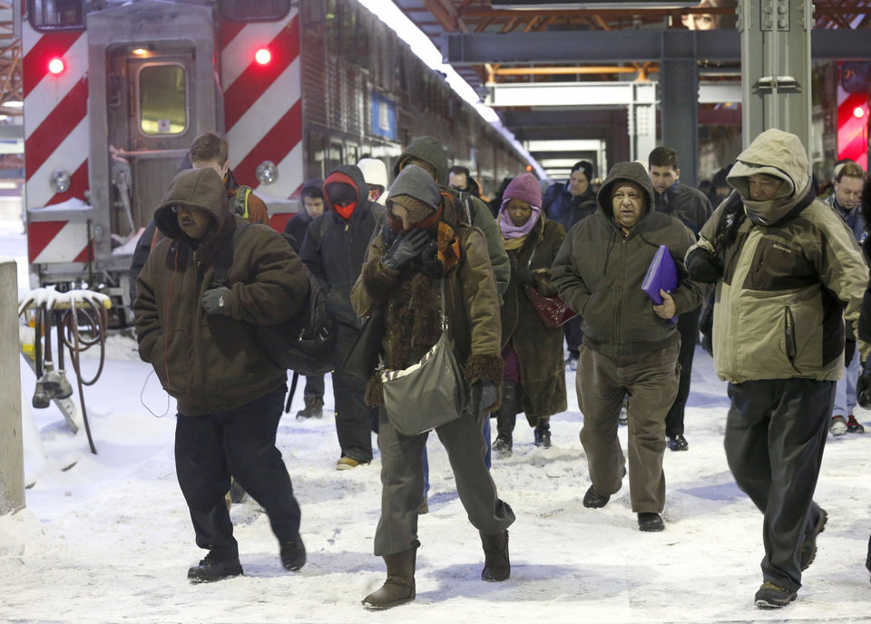 Photo - Commuters arrive at the La Salle Street commuter rail station as they experience temperatures well below zero and wind chills expected to reach 40 to 50 below, Monday, Jan. 6, 2014, in Chicago. (AP Photo/Charles Rex Arbogast)