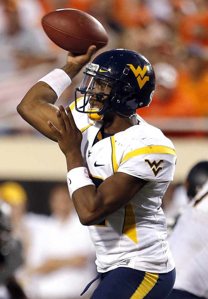 Photo - West Virginia's Geno Smith (12) throws a pass during a college football game between Oklahoma State University (OSU) and the West Virginia University at Boone Pickens Stadium in Stillwater, Okla., Saturday, Nov. 10, 2012. Photo by Sarah Phipps, The Oklahoman