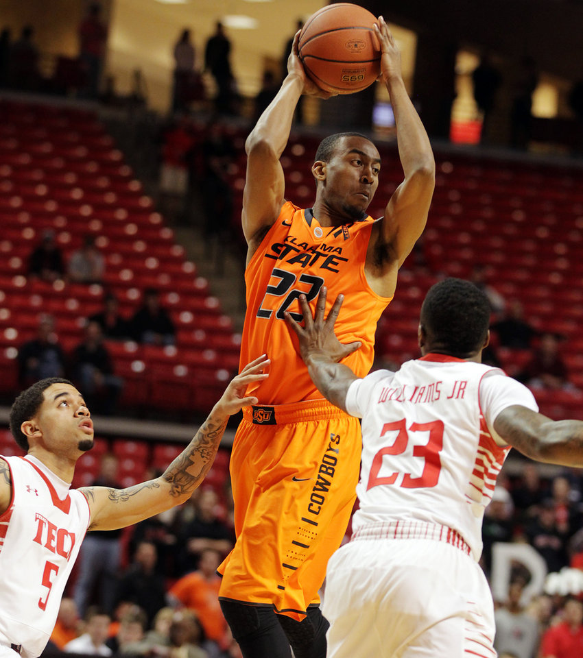 Oklahoma State\'s Markel Brown, center, passes under pressure from Texas Tech\'s Josh Gray (5) and Jamal Williams Jr., (23) during their NCAA college basketball game, Wednesday, Feb. 13, 2013, in Lubbock, Texas. (AP Photo/The Avalanche-Journal, Zach Long) ALL LOCAL TV OUT ORG XMIT: TXLUB101