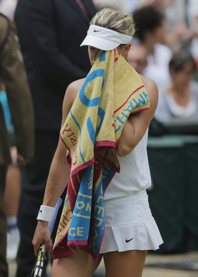 Photo - Eugenie Bouchard of Canada wipes her face with her towel as she walks back to the base line following a game break as she plays against Petra Kvitova of Czech Republic during the women's singles final at the All England Lawn Tennis Championships in Wimbledon, London, Saturday, July 5, 2014. (AP Photo/Pavel Golovkin)