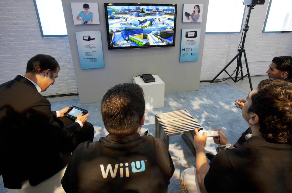 FILE - In this Thursday, Sept. 13, 2012 file photo, people demonstrate the Nintendo\'s Wii U GamePad and console in New York. Nintendo seeks to shake up gaming again with the Wii U touchscreen controller. (AP Photo/Mark Lennihan, File)