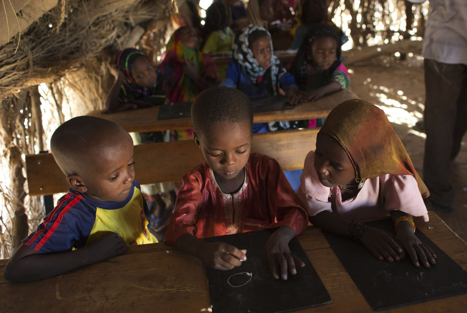 "In this Nov. 2, 2012 photo, 7-year-old Achta, right, and Youssouf, left, look on as Mahamat, center, struggles to copy a circle during a lesson on drawing the letter ""a"" in the village of Louri in the Mao region of Chad. In this village where malnutrition has become chronic, children have simply stopped growing. In the county that includes Louri, 51.9 percent of children are stunted, one of the highest rates in the world, according to a survey published by UNICEF - more than half the children in the village. (AP Photo/Rebecca Blackwell) ORG XMIT: NY873"