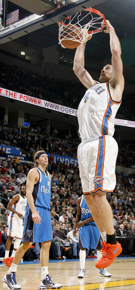 Photo - Oklahoma City's Nick Collison dunks the ball as Dirk Nowitzki of Dallas watches during the NBA basketball game between the Oklahoma City Thunder and the Dallas Mavericks at the Ford Center in Oklahoma City on Wednesday, December 16, 2009. Photo by Bryan Terry, The Oklahoman