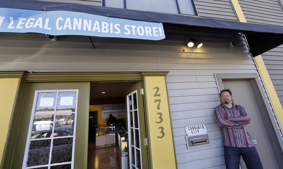 Photo - Cannabis City owner James Lathrop briefly leans against the exterior of his new recreational marijuana store Monday, July 7, 2014, in Seattle. The shop will be the first and, initially, only store in Seattle to legally sell recreational pot when sales begin Tuesday. (AP Photo/Elaine Thompson)