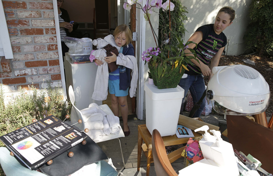 Photo - Seven-year-old Joey Bell helps clean out her mother's earthquake damaged hair salon as Stephanie Killingsworth, right, looks on Tuesday, Aug. 26, 2014, in Napa, Calif. The building that housed the salon was declared unsafe and red tagged. The earthquake that jolted California's wine capital may have caused at least $1 billion in property damage, but it also added impetus to the state's effort to develop an early warning system that might offer a few precious seconds for residents to duck under desks, trains to slow down and utility lines to be powered down before the seismic waves reach them. The magnitude-6.0 quake struck early Sunday near the city of Napa. (AP Photo/Eric Risberg)