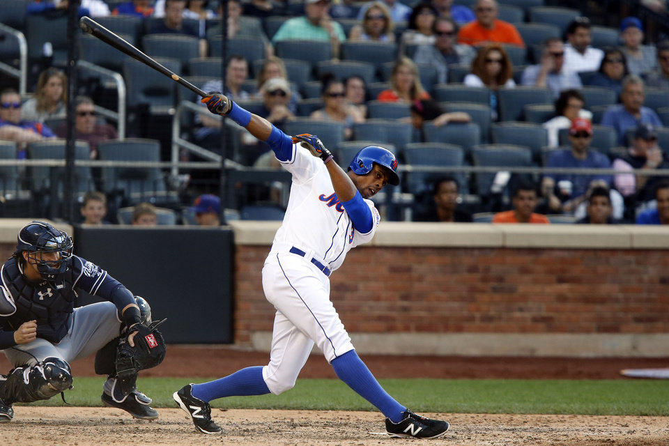 Photo - New York Mets' Curtis Granderson, right, swings and misses during the seventh inning of a baseball game against the San Diego Padres, Saturday, June 14, 2014, in New York. (AP Photo/Jason DeCrow)