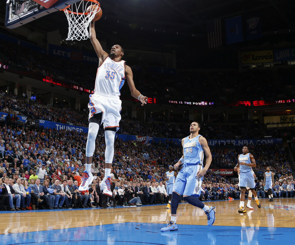 Oklahoma City\'s Kevin Durant dunks the ball in front of Denver\'s JaVale McGee during an NBA basketball game between the Oklahoma City Thunder and the Denver Nuggets at Chesapeake Energy Arena in Oklahoma City, Tuesday, March 19, 2013. Photo by Bryan Terry, The Oklahoman