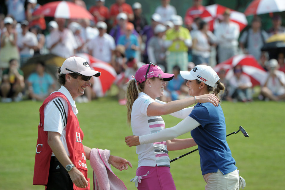 Photo - Paula Creamer of the U.S.A., center, and Azahara Munoz of Spain, right, embrace each other as Creamer's caddie Colin Cann, left, smiles after Creamer won the HSBC Women's Champions golf tournament in Singapore on Sunday, Mar. 2, 2014. (AP Photo/Joseph Nair)