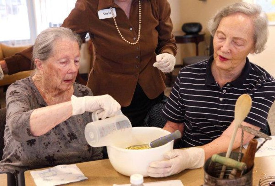 Photo - Florence Clary, left, and Emily Raines work on pumpkin bread at Touchmark at Coffee Creek.  JIM BECKEL - THE OKLAHOMAN