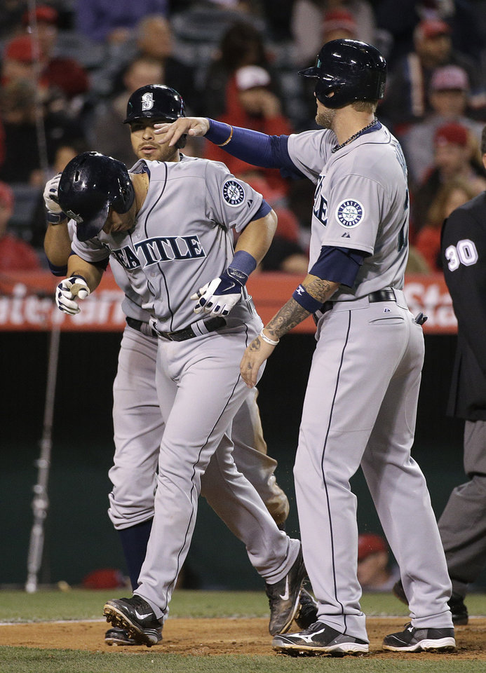 Photo - Seattle Mariners' Mike Zunino, left, is congratulated by Corey Hart, right, and Stefen Romero after hitting a three-run home run during the sixth inning of a baseball game against the Los Angeles Angels on Wednesday, April 2, 2014, in Anaheim, Calif. (AP Photo/Jae C. Hong)