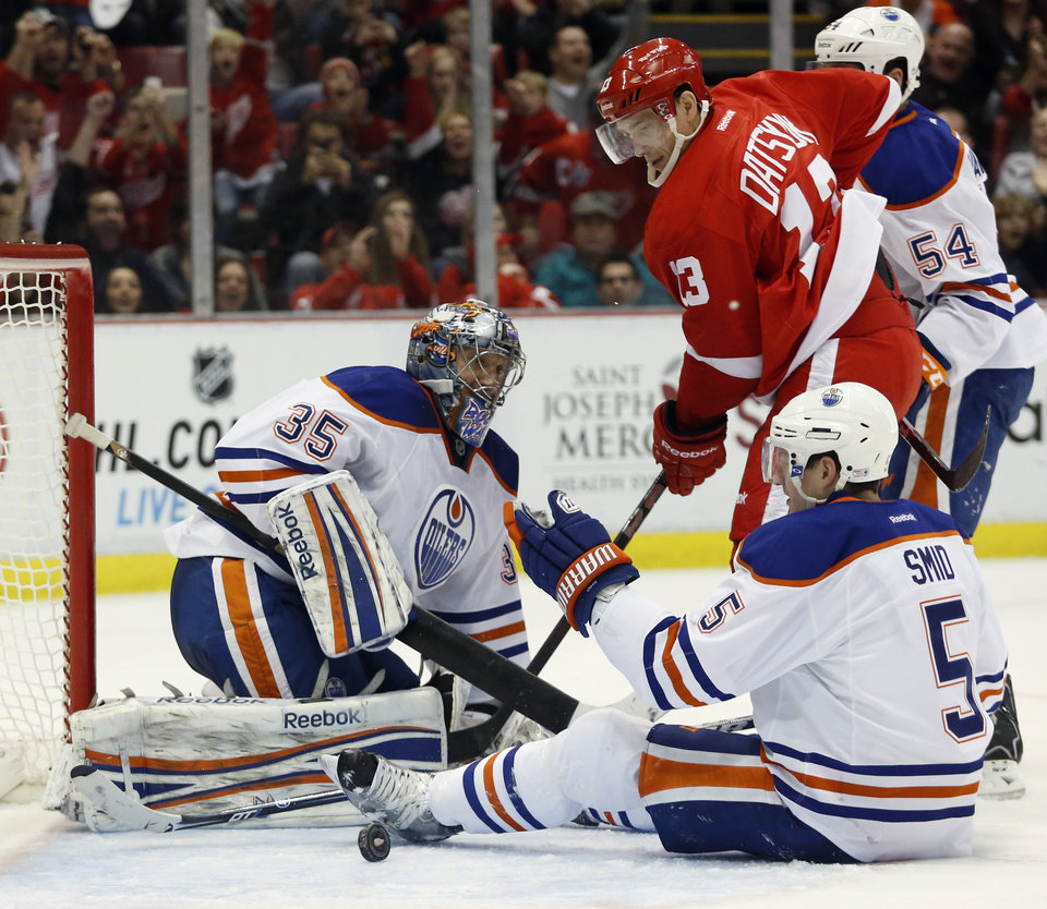 Detroit Red Wings center Pavel Datsyuk (13), of Russia, watches the puck bounce out of the net after scoring against Edmonton Oilers goalie Nikolai Khabibulin (35), of Russia, and defenseman Ladislav Smid (5), of Czechoslovakia, in the second period of an NHL hockey game Saturday, Feb. 9, 2013, in Detroit. (AP Photo/Duane Burleson)