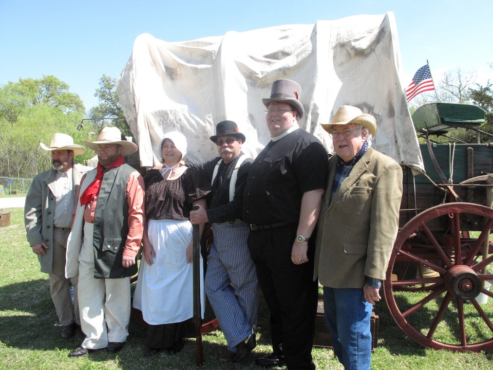 Photo - From left, Chip Hancock, Robbie Rattan, Kathy Rattan, Phil Rattan, the Rev. John Malget and the Rev. Jeff Hamilton stand near a covered wagon on the lawn of First Christian Church of Oklahoma City (Disciples of Christ) during the church's 124th anniversary celebration  on April 21. Photo provided by Carla Hinton, The Oklahoman