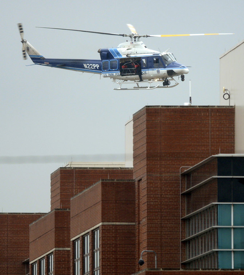 Photo - A U.S. Park Police helicopter flies over a building at the Washington Navy Yard in Washington, Monday, Sept. 16, 2013. At least one gunman opened fire inside a building at the Washington Navy Yard on Monday morning, (AP Photo/Susan Walsh)