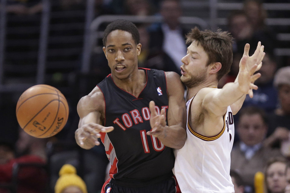 Photo - Toronto Raptors' DeMar DeRozan, left, passes against Cleveland Cavaliers' Matthew Dellavedova, from Australia, during the fourth quarter of an NBA basketball game Tuesday, March 25, 2014, in Cleveland. Cleveland defeated Toronto 102-100. (AP Photo/Tony Dejak)