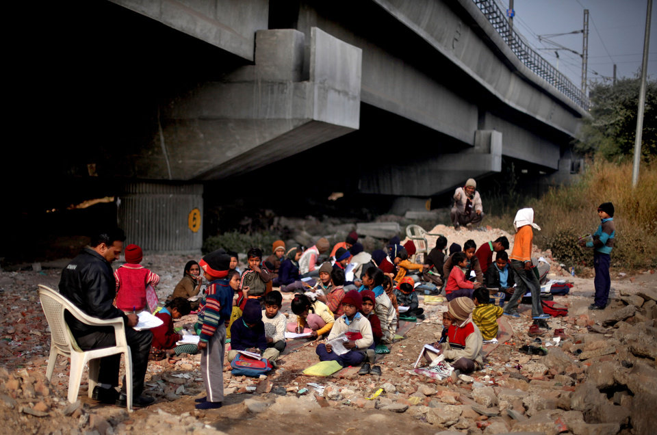 Indian underprivileged children attend a free school in the open, run under a metro bridge, on a cold morning in New Delhi, India, Tuesday, Jan. 8, 2013. North India continues to face below average weather conditions with dense fog affecting flights and trains. More than 100 people have died of exposure as northern India deals with historically cold temperatures. (AP Photo/Altaf Qadri)