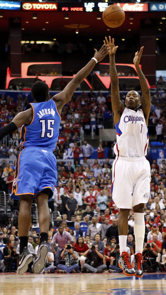 Photo - Los Angeles' Jamal Crawford (11) takes a three-point shot against Oklahoma City's Reggie Jackson (15) with 1:25 left in the fourth quarter during Game 4 of the Western Conference semifinals in the NBA playoffs between the Oklahoma City Thunder and the Los Angeles Clippers at the Staples Center in Los Angeles, Sunday, May 11, 2014. Photo by Nate Billings, The Oklahoman