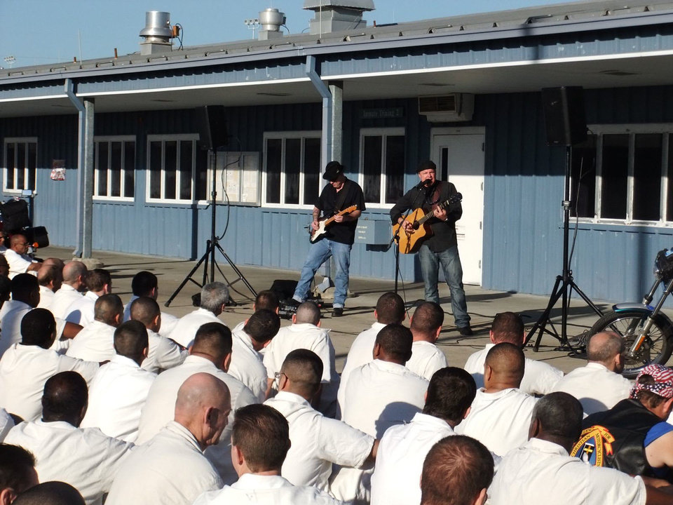 Inmates listen as contemporary Christian recording artist Matthew Blagg, at far right, performs a song in a prison yard as part of the Bill Glass Weekend of Champions. Photo provided