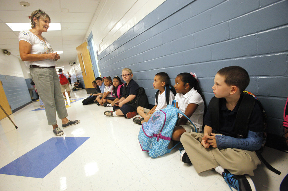 Photo - First grade teacher Sundae Osborn greets her students lined up in the hallway waiting to enter their classroom as classes start for the day at Adams Elementary in Oklahoma City Wednesday, Aug. 1, 2012. Wednesday was the first day of classes in the Oklahoma City Public School District.  Photo by Paul B. Southerland, The Oklahoman