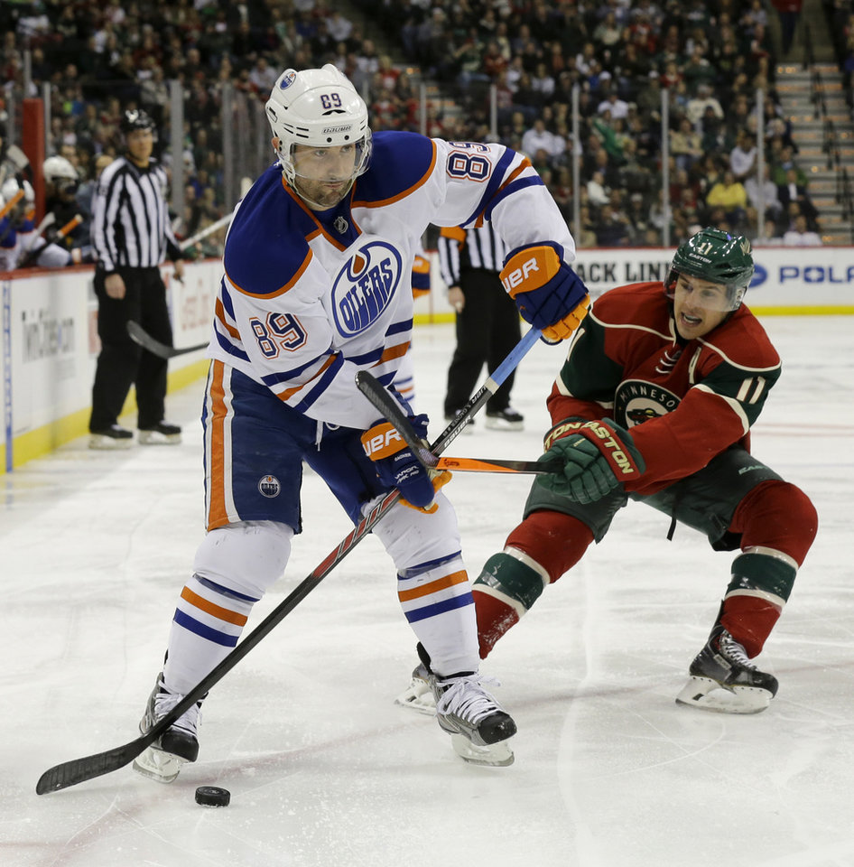 Photo - Edmonton Oilers center Sam Gagner (89) controls the puck in front of Minnesota Wild left wing Zach Parise (11) during the second period of an NHL hockey game in St. Paul, Minn., Tuesday, March 11, 2014. (AP Photo/Ann Heisenfelt)