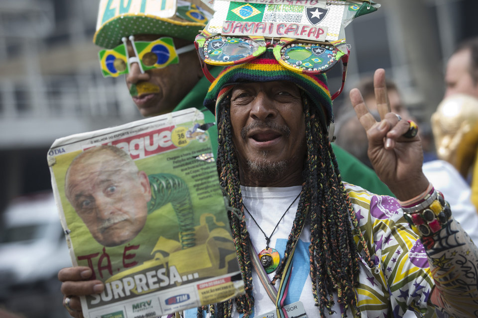 Photo - A Brazil soccer fan holds up a newspaper with a photo of Brazil's coach Luiz Felipe Scolari and flashes a victory sign outside the venue where coach Luiz Felipe Scolari is announcing his squad for the upcoming international soccer tournament in Rio de Janeiro, Brazil, Wednesday, May 7, 2014. The team will mix talented young stars such as Neymar and Oscar with more experienced players such as Dani Alves, David Luiz, Thiago Silva and Hulk. Past stars such as Ronaldinho, Kaka and Robinho were left off the squad as expected. (AP Photo/Silvia Izquierdo)