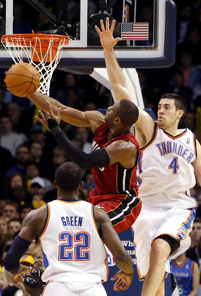 Photo - Miami's Dwyane Wade puts up a shot despite pressure from Oklahoma City's Nick Collison during their NBA basketball game at the OKC Arena in Oklahoma City on Thursday, Jan. 30, 2011. The Heat beat the Thunder 108-103. Photo by John Clanton, The Oklahoman