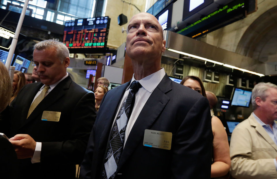 Photo - Former New York Rangers hockey player and general manager Mark Messier, center, looks over the New York Stock Exchange trading floor, Friday, June 20, 2014 before opening bell ceremonies to mark the first day of trading of Performance Sports Group, Friday, June 20, 2014. (AP Photo/Richard Drew)