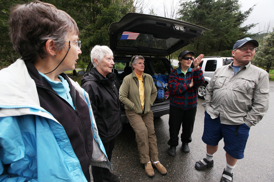 Photo -   A group of hikers talks about their proposed hike at a trailhead several miles from where a gun-toting survivalist is suspected of killing his wife and daughter several days earlier Friday, April 27, 2012, in North Bend, Wash. From left are Jane Falding, Sally Betts, Dixie Green and Judy and Roy Hines. Peter Alex Keller may be holed up in a self-made fort not far from where Seattle's outer suburbs give way to the vast recreational playground of Cascade Mountains. Police expect more people to hit the nearby trails this weekend, and deputies are warning them to steer clear of Keller if they think they see him. (AP Photo/Elaine Thompson)