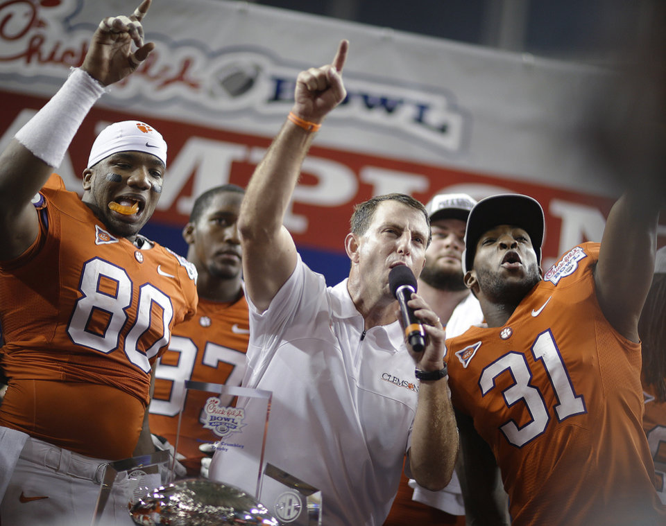 Clemson coach Dabo Swinney speaks to fans with safety Rashard Hall (31) and tight end Brandon Ford (80) after the Chick-fil-A Bowl NCAA college football game against LSU, Monday, Dec. 31, 2012, in Atlanta. Clemson won 25-24. (AP Photo/David Goldman)